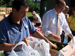 Photo of Assemblyman Burzichelli and Secretary Fisher bagging Jersey produce