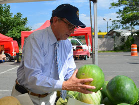 Photo of Secretary Fisher choosing a watermelon - Click to enlarge