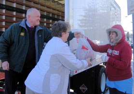 Photo of Secretary Kuperus and Elaine Britcher of the Interfaith Food Pantry giving a turkey to a client - Click to enlarge