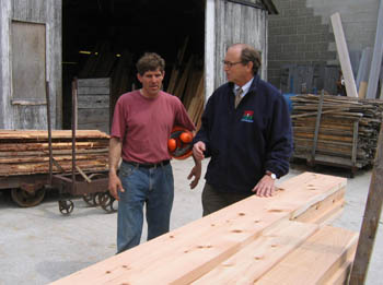 Paul Schairer and Secretary Fisher look at wood milled from NJ trees