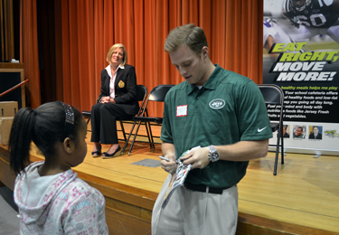 Photo of Greg McElroy awarding a prize at Hess School