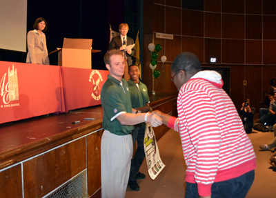 Photo of Greg McElroy and Julian Posey awarding a prize to a student during the Eat Right, Move More Program