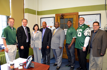 Photo of officials gathered with NY Jets players Greg McElroy and Julian Posey
