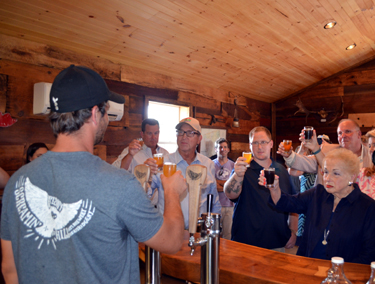 Photo of Secretary Fisher offering a toast to the new brewery