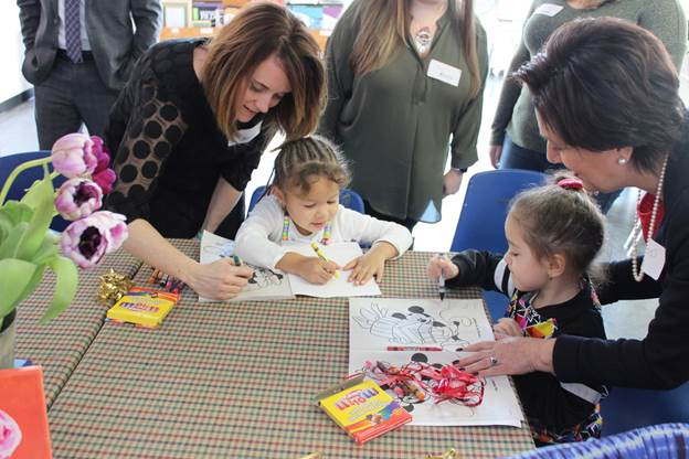 Commissioner Kimberley Harrington and Acting Chief Academic Officer Laura Morana help children at the HomeFront Family Campus in Ewing open their new coloring books and crayons donated by New Jersey Department of Education staff.