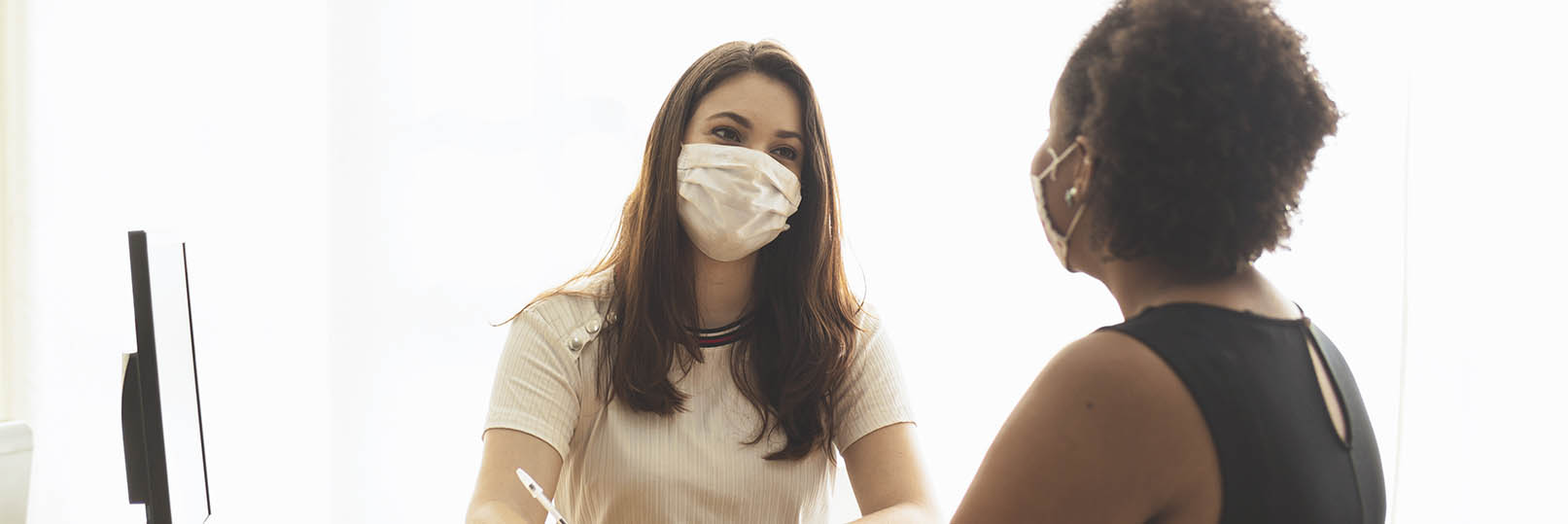 two women wearing masks at a job interview