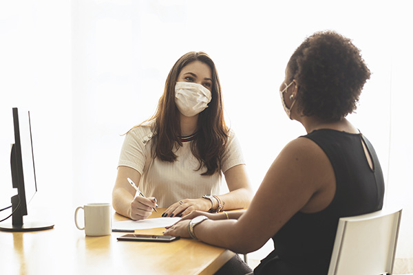 two women wearing face masks in an office for a job interview