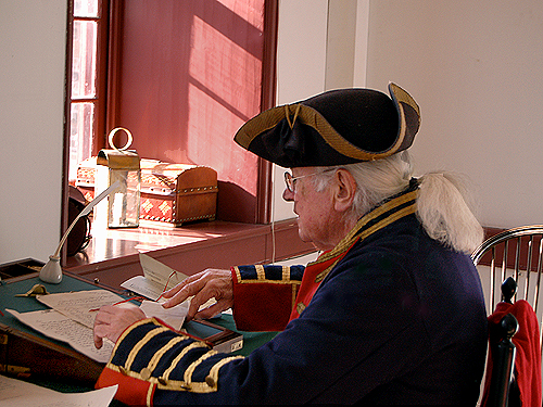 The Officer of the Day prepares work orders at his desk in the officers' quarters