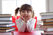 kid with hands supporting head at a desk full of books.