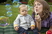 photo of Mom blowing bubbles for son