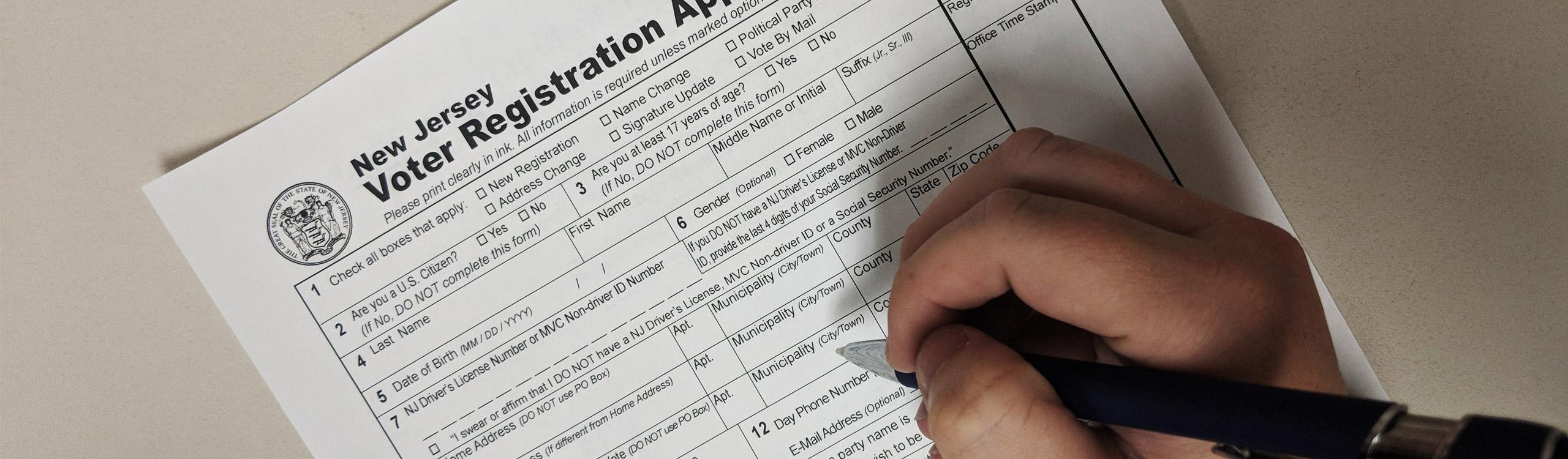 Register Vote - Image of Hand filling out Registration Form